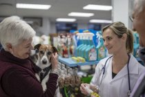 Senior woman and man with dog in shop at veterinarian — Stock Photo
