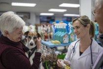 Старшая женщина и мужчина с собакой в магазине у ветеринара — стоковое фото