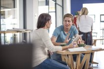 Man and woman talking in a cafe with digital tablet — Stock Photo