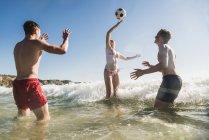Amigos brincando com uma bola no mar — Fotografia de Stock