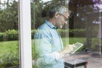 Reifer Mann mit digitalem Tablet hinter Fensterscheibe — Stockfoto