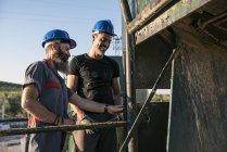 Two mechanics wearing helmets working outdoors — Stock Photo
