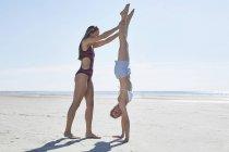 Молодая женщина, помогая другу делать стойку на пляже — стоковое фото