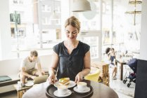 Waitress in cafe serving cake and coffee on tray — Stock Photo