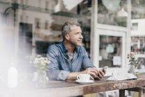 Homme d'âge mûr assis dans le café — Photo de stock