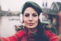 Alemania, Colonia, retrato de mujer con orejeras tomando selfie - foto de stock