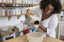 Женщина, работающая с глиной в керамической мастерской — стоковое фото