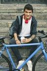 Adolescente con una bici fixie seduto su gradini con caffè da andare, sorridente alla fotocamera — Foto stock