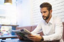 Businessman sitting in cafe and reading newspaper — Stock Photo