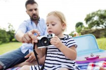 Father showing his little daughter how to use camera — Stock Photo