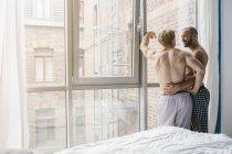 Pareja Gay abrazando en ventana - foto de stock