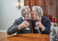 Senior couple holding red wine glasses and kissing — Stock Photo