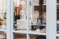 Young businessman and woman using laptop in a cafe — Stock Photo