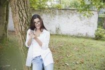 Jeune femme avec le smartphone appuyé contre le tronc d'arbre — Photo de stock