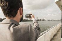 Uomo in traghetto sull'East River che scatta foto, New York, Stati Uniti — Foto stock