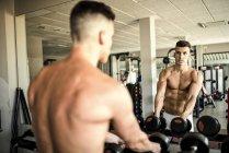 Mann Heben von Gewichten vor Spiegel — Stockfoto