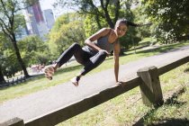 Femme sautant par-dessus la clôture dans le parc — Photo de stock