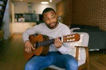 Junger Mann zu Hause spielt Gitarre — Stockfoto