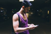 Side view of handsome caucasian sporty man using smartphone — Stock Photo