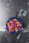 Winter salad with red cabbage, tangerine and chick-peas on served blue plate — Stock Photo