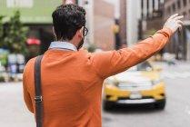 Empresario llamando a taxi amarillo, Ciudad de Nueva York, EE.UU. - foto de stock