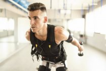 Man training with electrical muscle stimulation in gym — Stock Photo