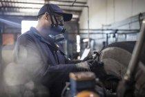 Reparador de pneus usando máscara esculpir pneu com máquina de corte de piso na fábrica — Fotografia de Stock