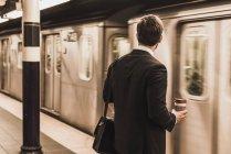 Giovane uomo d'affari in attesa alla stazione della metropolitana piattaforma e tenendo tazza usa e getta — Foto stock
