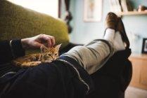 Женщина лежит на диване и гладит котенка на коленях — стоковое фото