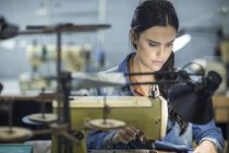 Seamstress in clothing factory sewing clothes — Stock Photo