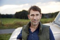 Portrait d'un homme debout à côté de van dans la nature — Photo de stock
