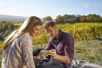 Giovane coppia in un vigneto condividere il cellulare — Foto stock