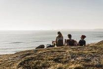 Вид сзади трех друзей отдыха на берегу моря — стоковое фото