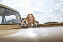Femme assise dans un van et regardant la vue — Photo de stock