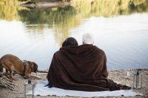 Couple de personnes âgées détendue avec chien à un lac — Photo de stock