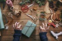 Mujer envolviendo regalos de Navidad en la mesa de madera con objetos de decoración - foto de stock