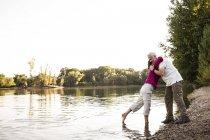 Старший пара обіймати на озері — стокове фото