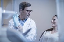 Professional caucasian dentist preparing treatment putting on surgical gloves — Stock Photo