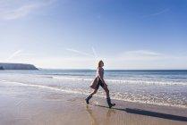 Blond teenage girl walking on the beach — Stock Photo