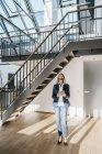Femme d'affaires avec de longs cheveux gris en utilisant une tablette dans un loft — Photo de stock