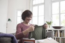 Smiling woman sitting on sofa at home and looking at garment — Stock Photo