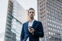 Портрет бізнесмен з смартфон стоячи в місті — стокове фото