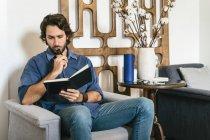 Homme d'affaires assis dans le salon de bureau et regardant cahier — Photo de stock