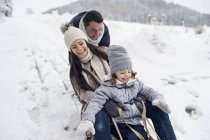 Happy family on sledge in winter landscape — Stock Photo