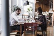 Joven hombre y mujer con ordenador portátil y tablet en un café - foto de stock