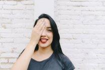 Ritratto di giovane donna davanti al muro di mattoni che copre un occhio con mano — Foto stock