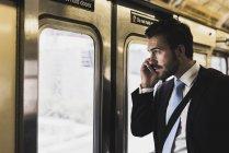 Joven hombre de negocios tomando metro y usando smartphone - foto de stock