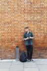 Giovane hipster bello in piedi contro muro di mattoni con smartphone — Foto stock