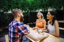 Happy friends drinking spritzer at outdoor pub — Stock Photo