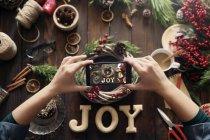 Manos de la mujer tomar fotografía de creación propia corona de Adviento con smartphone - foto de stock